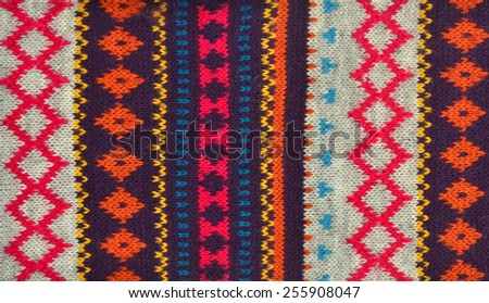Close up on knit woolen texture. Colorful geometric shapes pattern as a background.