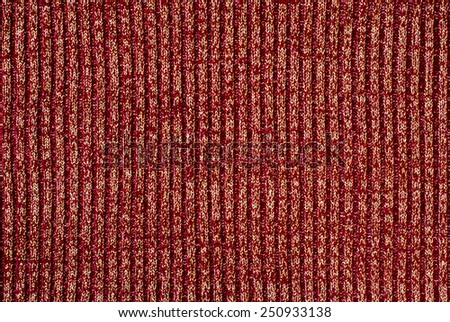 Close up on knit woolen texture. Dark red and gold woven thread as a background. - stock photo