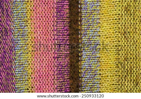 Close up on knit woolen texture. Pink and yellow woven thread sweater as a background. - stock photo