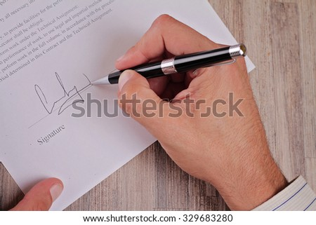 Close up on male hand put a signature on an  credit agreement. Business Man Signing A Contract. Lawyer, realtor. - stock photo