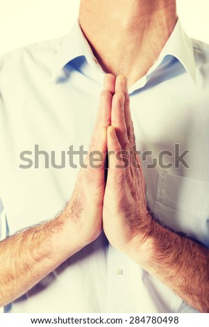 Close up on male hands clenched to pray. - stock photo