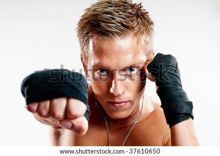 Close up on male kick-boxer punshing isolated on white background - stock photo