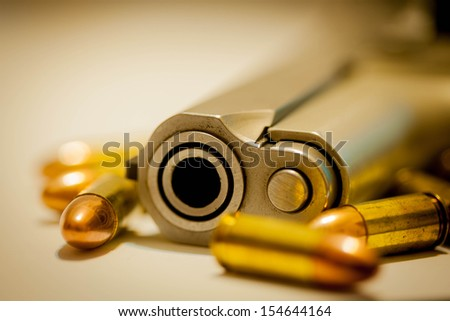 close-up on 9mm ammo with a handgun. - stock photo