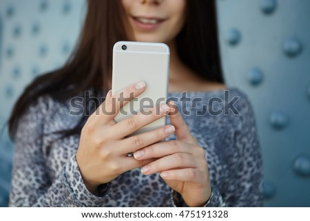 Close up on mobile phone in hands of young girl. Modern silver gadget with big screen