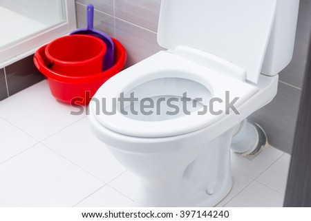 Close up on open toilet in bathroom with white and gray tiles next to red cleaning buckets and dust pan - stock photo