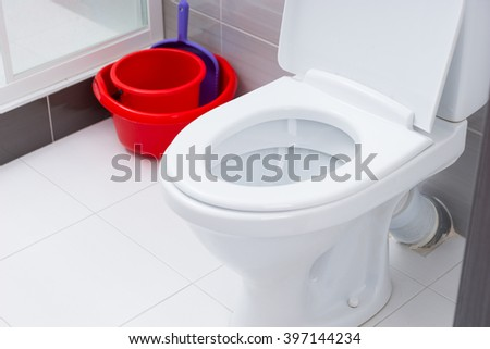 Close up on open toilet in clean bathroom with white and gray tiles next to red cleaning buckets and dust pan - stock photo