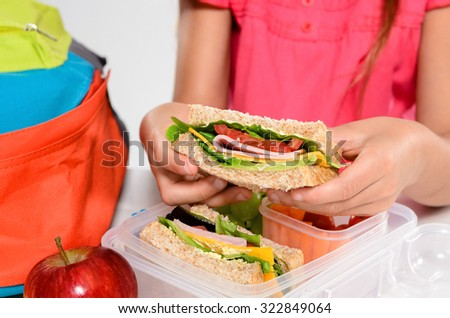 Close up on pair of young girl's hands removing a healthy wholesome wholemeal bread ham sandwich from her lunch box during break time recess - stock photo