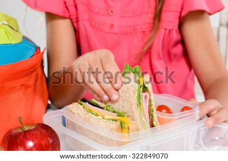 Close up on pair of young girl's hands removing a healthy wholesome wholemeal bread ham sandwich from her lunch box during lunch period - stock photo