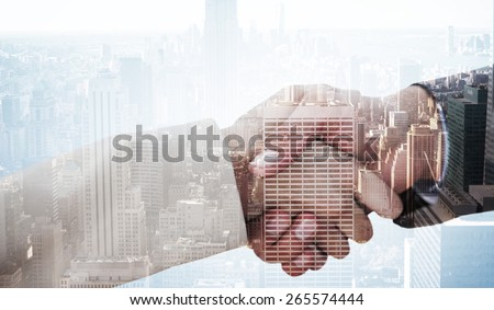 Close up on partners shaking hands against city skyline - stock photo