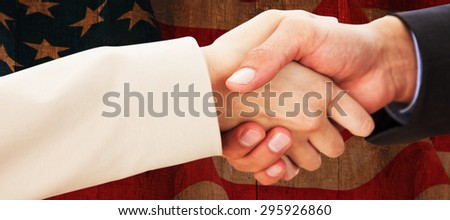 Close up on partners shaking hands against weathered oak floor boards background