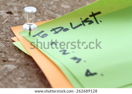 close up on pin and to do list word on sticky note with cork board as concept - stock photo