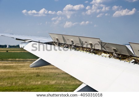 Close up on plane wing spoiler at landing - stock photo
