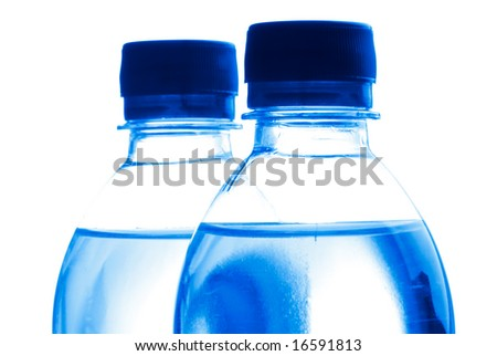 Close-up on plastic bottles of water isolated on white, blue toning. - stock photo