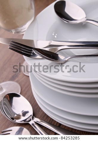close up on plates stack and cutlery - stock photo