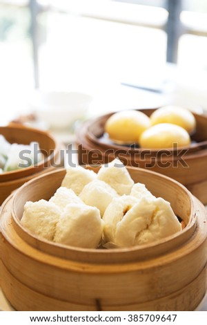 Close-up on pork bun and variety of dim sum in bamboo steam containers.