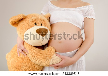 Close up on pregnant belly and a big teddy bear. Woman expecting a baby with a cute teddy bear huging her belly. - stock photo