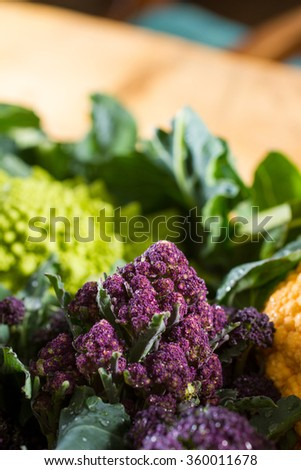 Close up on purple broccoli, with yellow cauliflower and romanesco cauliflower in the background and foreground. Wonderful contrast of complementary colours.