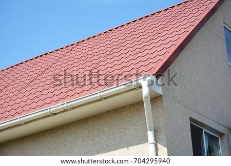 Close Up On Red Metal Roof With White, Plastic Rain Gutter System. Roofing  Construction