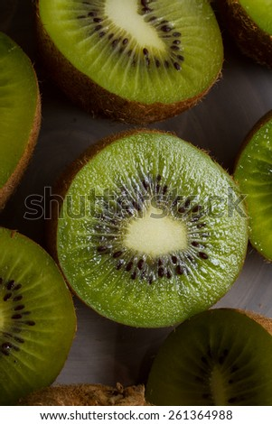 Close up on ripe half kiwi fruits one a grey plate. Healthy eating. - stock photo