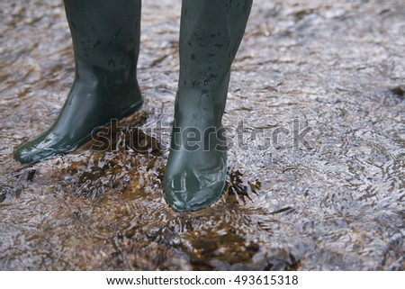 close up on  rubber boots in the water