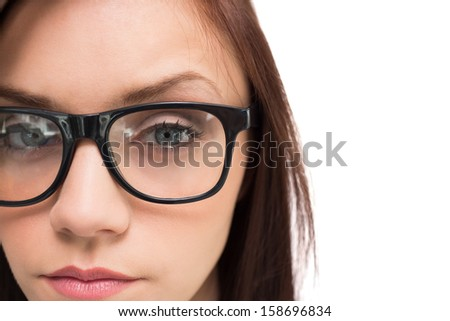 Close up on serious brunette with glasses posing on white background