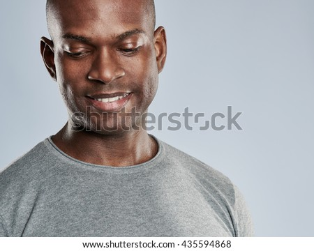Close up on single attractive grinning Black man with shaved head in gray shirt looking downward over background with copy space