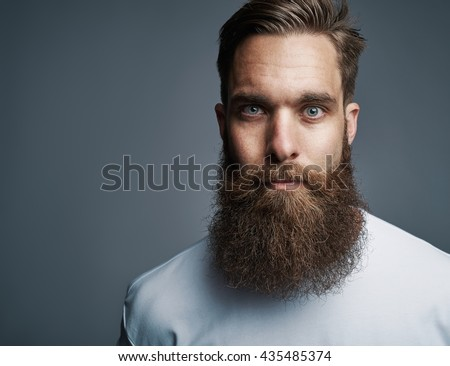 Close up on single serious handsome young Caucasian man with muscular build and well groomed beard over gray background - stock photo