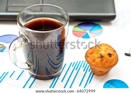Close-up on stock market data charts, coffee and cake