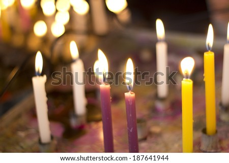 Close up on the candle of an improvised chapel's altar. - stock photo