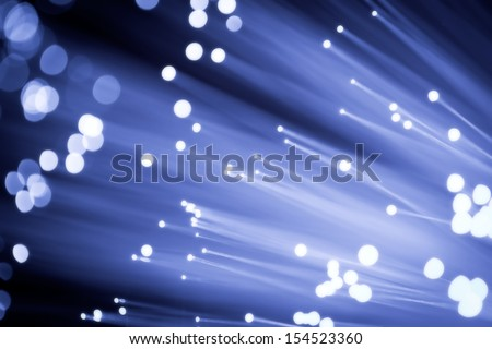 Close up on the ends of a selection of illuminated blue fiber optic light strands with black background. - stock photo