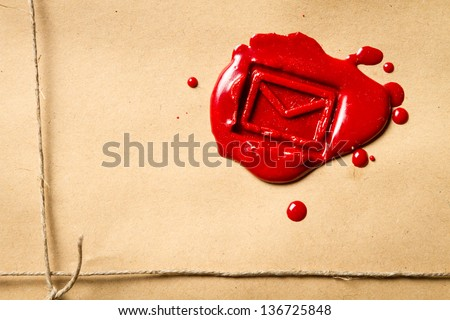 Close-up on the envelope symbol imprinted in red sealing wax - stock photo