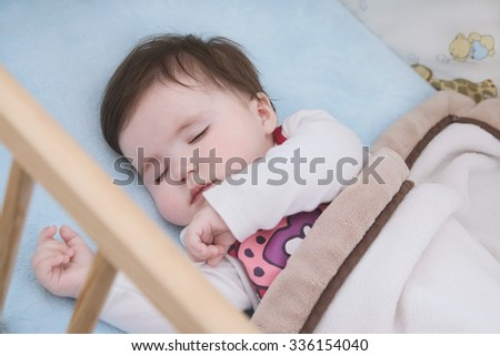 Close up on the face of sleeping child in her cot