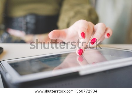Close up on the hand of a young handsome caucasian girl using technological devices like tablet, tapping the screen - multitasking, technology concept - stock photo