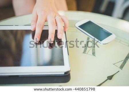 Close up on the hand of a young handsome caucasian girl using technological devices like tablet and smartphone - multitasking, technology concept - stock photo