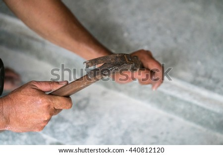 Close up on the hands of a person using a hammer