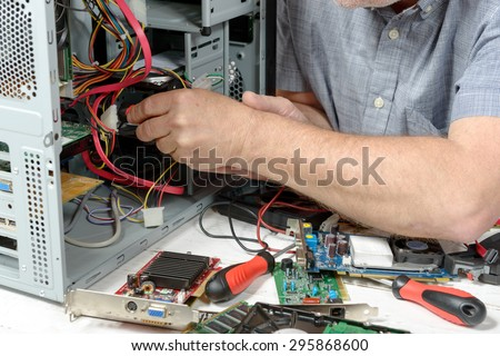 close-up on the hands of the technician repairing a computer - stock photo