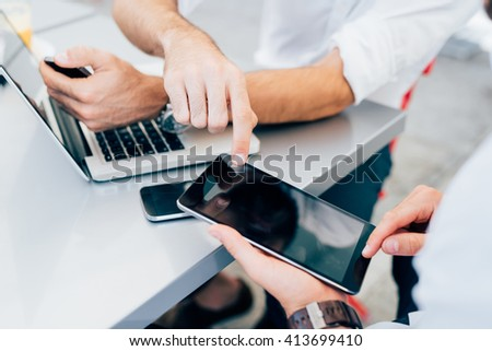 Close up on the hands of two men using technological devices, tapping the screen of a tablet hand hold - technology, communication, multitasking concept