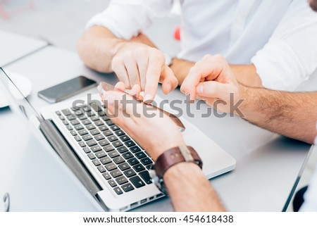 Close up on the hands of two men using technological devices, tapping the screen of a tablet hand hold - technology, communication, multitasking concept - stock photo