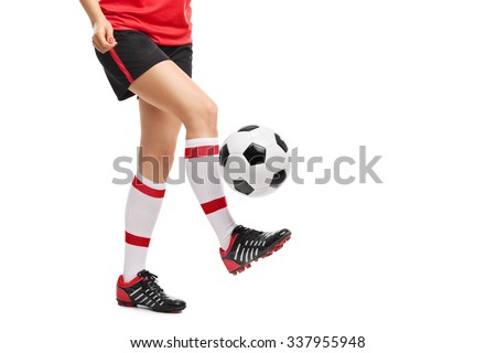 Close-up on the legs of a female football player jugling with a ball isolated on white background  - stock photo
