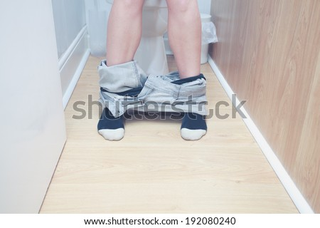 Close up on the legs of a woman sitting on the toilet