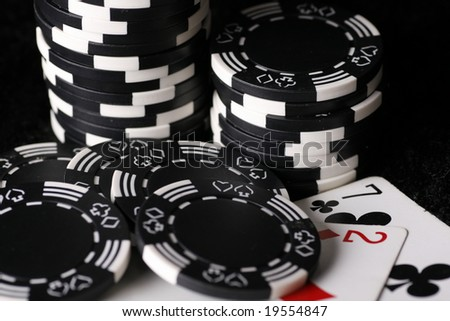 Close up on the worst possible starting hand in texas holdem poker with casino chips in background. - stock photo