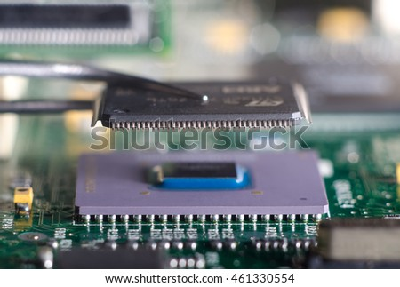 Close up on tweezers holding chip on computer circuit board