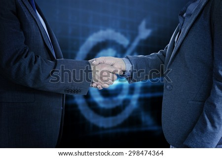 Close up on two businesspeople shaking hands against digital target - stock photo