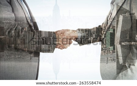 Close up on two businesspeople shaking hands against room with large window looking on city - stock photo