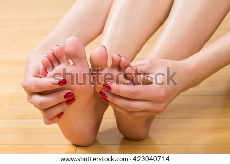 Close up on unidentifiable woman massaging her own feet with neatly manicured and painted fingers - stock photo