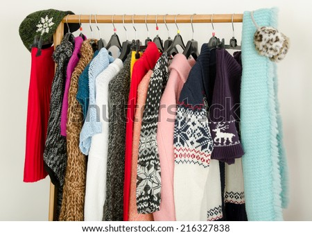 Close up on wardrobe with winter clothes nicely arranged. Dressing closet with colorful clothes and accessories on hangers. - stock photo