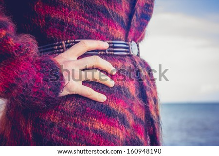 Close up on woman in woolen jumper on the beach - stock photo