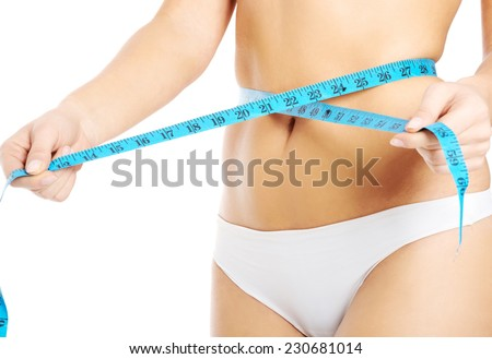 Close up on woman measuring her waist. - stock photo