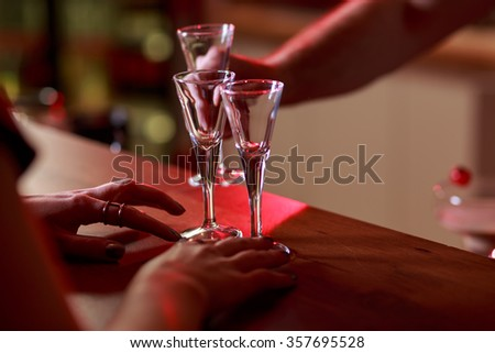 Close-up on woman's hand and empty glasses on the bar - stock photo
