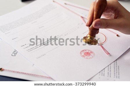 Close up on woman's notary public hand ink stamping the document. Notary public concept